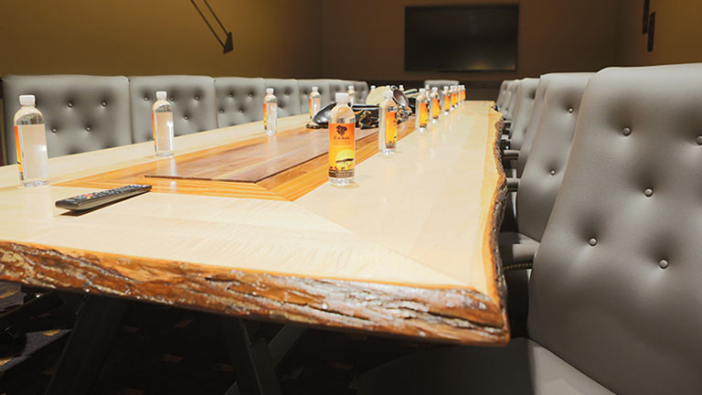 Raw wood table top with grey leather chairs set for an executive meeting at Kalahari Resorts and Conventions