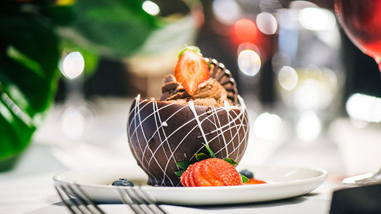Chocolate mousse in a chocolate cup garnished with sliced strawberry
