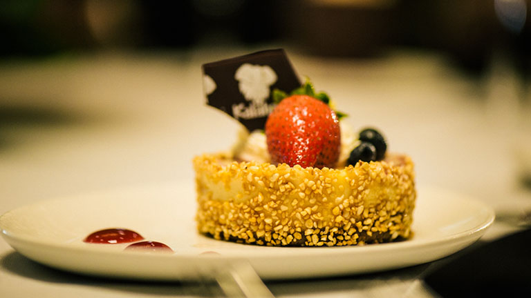 small plate with chocolate crusted cheesecake topped with strawberry