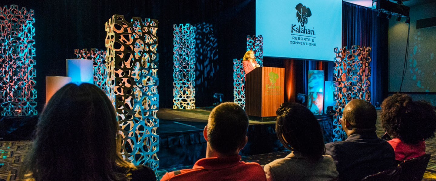 Female speaker at a podium on stage during a large event at Kalahari Resorts and Conventions