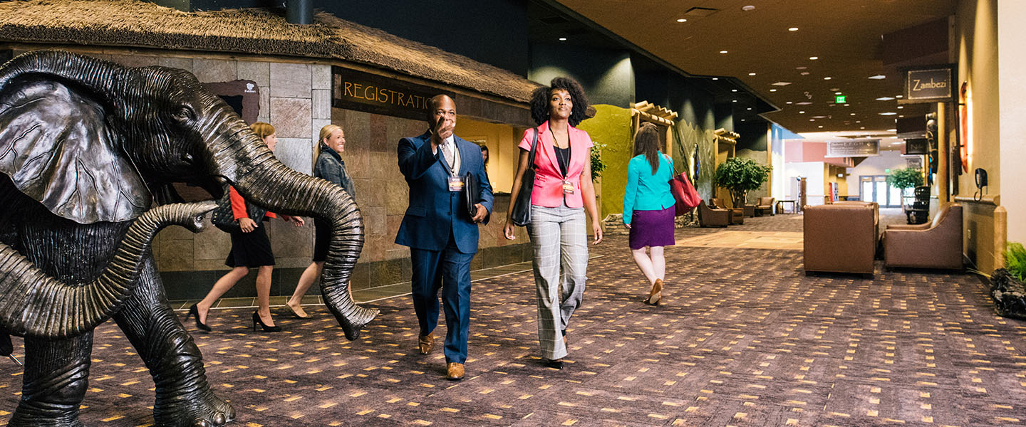 Two event attendees walking past the registration counter at Kalahari Resorts and Conventions