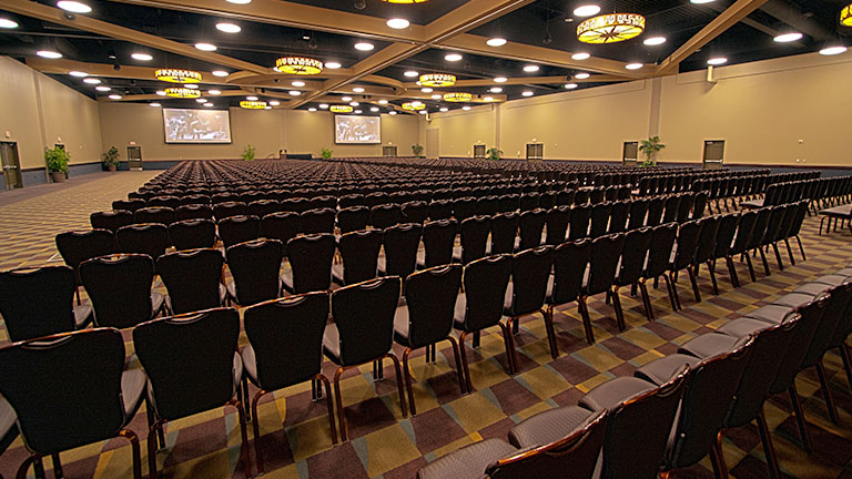 The Kalahari Ballroom set up for a large meeting with many rows of chairs and two drop down screens
