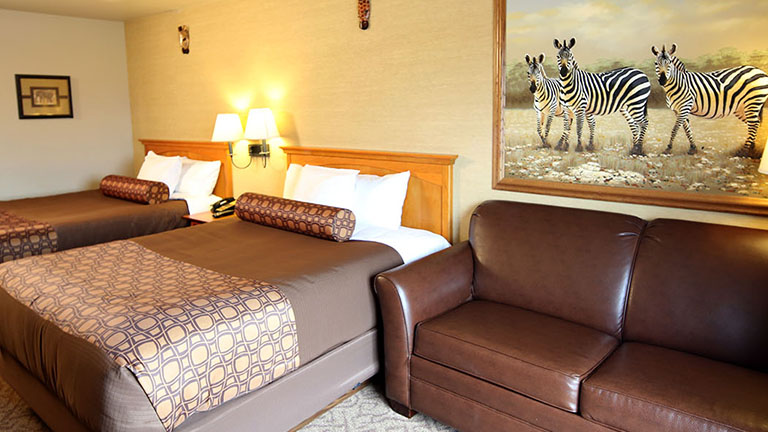 Inside a Single Room at Kalahari, two beds, a leather love seat and a beautiful zebra painting