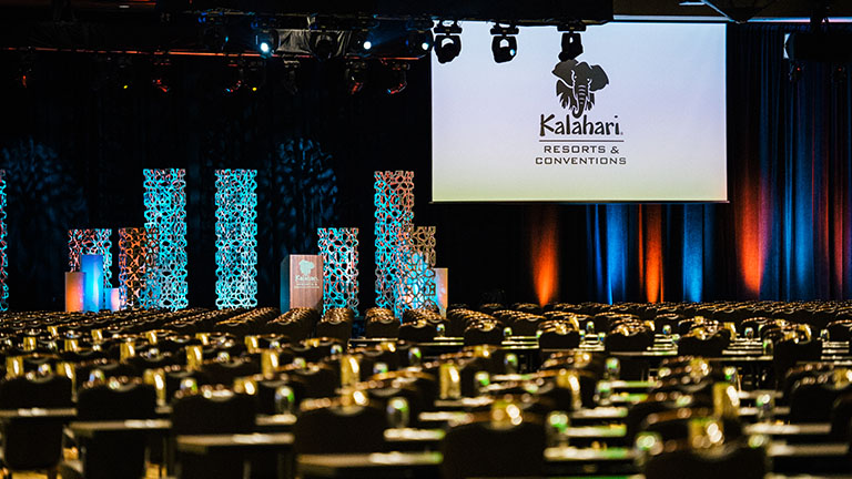 A ballroom set up for a large event with a podium and large dropdown screen at the stage